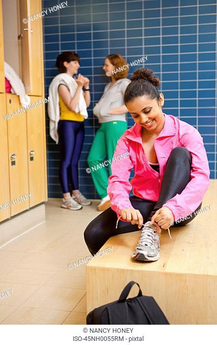 Woman tying her shoes in locker room