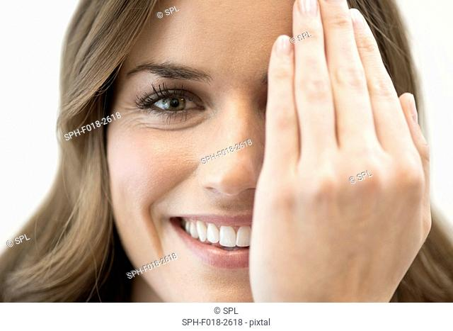 Mid adult woman covering eye with hand