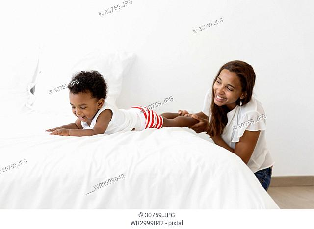 Smiling woman playing on a bed with young boy wearing stripy shorts