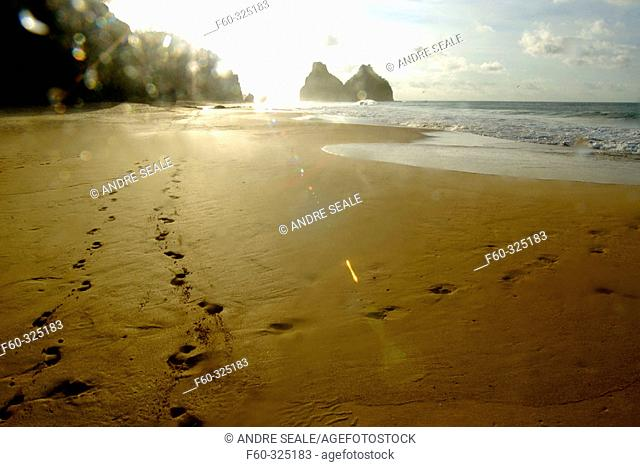 Footprints in Cacimba do Padre beach and Dois Irmãos islands in background, Fernando de Noronha national marine sanctuary. Pernambuco state, Brazil
