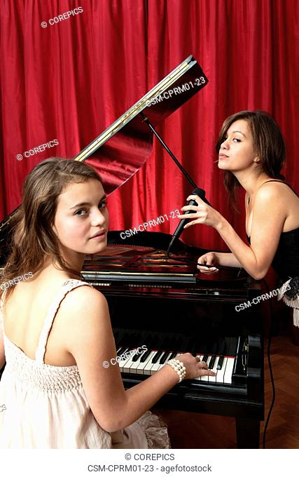 Two young women performing a piano recital, accompanied by vocals on a stage in front of a red curtain