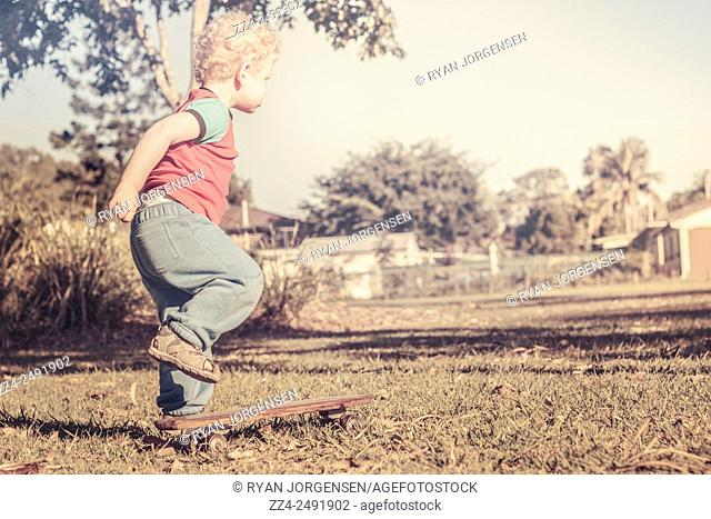 Authentic faded brown vintage image of an adorable three year old child determined to skateboard on a wooden 1950s deck on grass field surface