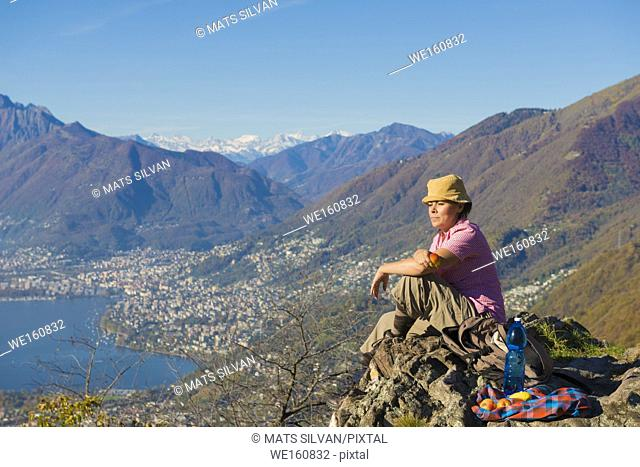 Woman Eating An Apple On Mountain Top in Ticino, Switzerland