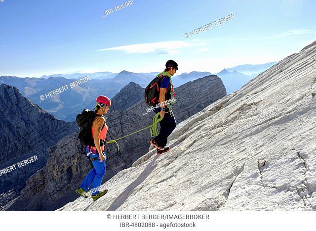 Mountain guide guiding a young woman on a short rope through a rock face, Wiederroute, Watzmann, Schönau am Königsee, Berchtesgadener Land, Bavaria, Germany