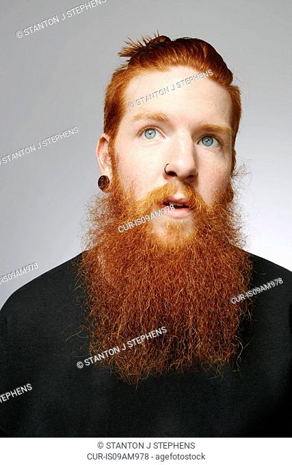 Studio portrait of young man with blue eyes, red hair and overgrown beard