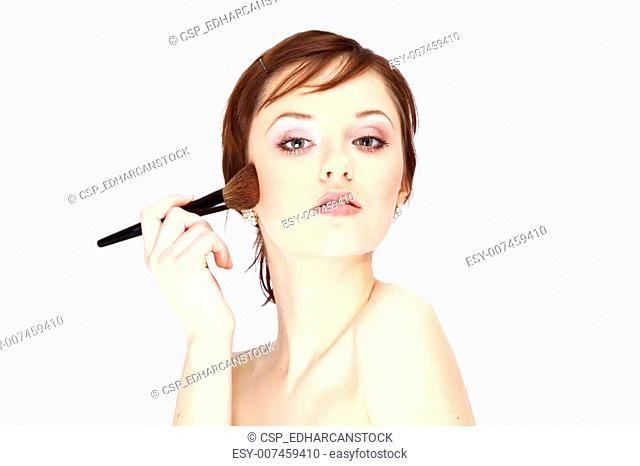 Portrait of attractive young woman applying blusher