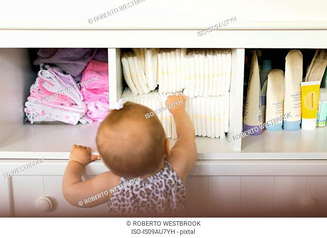 Rear view of baby girl reaching for diaper in cupboard