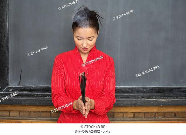 Asian woman is holding chopsticks in front of a blackboard
