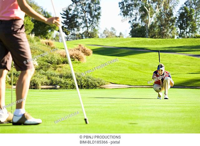 Women planning putt on green at golf course