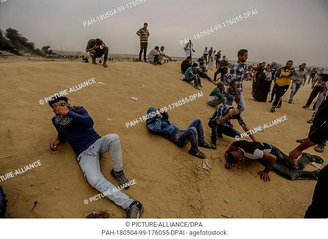 dpatop - Palestinian protesters take cover from Israeli tear gas during clashes with Israeli security forces along the Israel-Gaza border, east of Khan Yunis