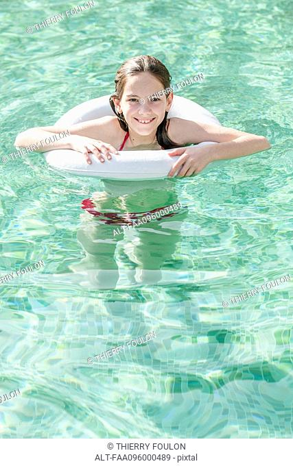 Girl floating in swimming pool, portrait
