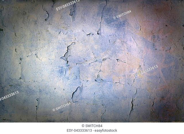 A wall with cracked blue and violet paint. Beautiful bright background with vignette. Texture of old cover with cracks