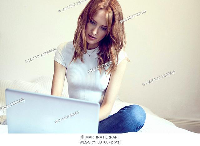 Redheaded woman sitting on bed using laptop