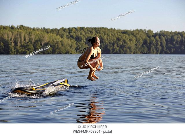 Woman jumping into water from paddleboard