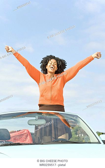 African woman with arms raised in convertible car