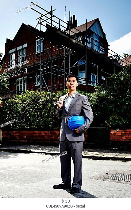 Man wearing suit, holding hard hat, standing outside house with scaffolding
