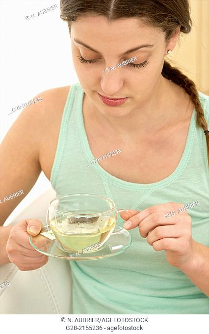 young beautiful woman holding a glass cup of herb tea with a slice of lemon, suffering from a cold