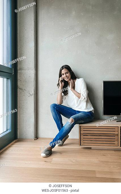 Portrait of smiling woman on cell phone at home