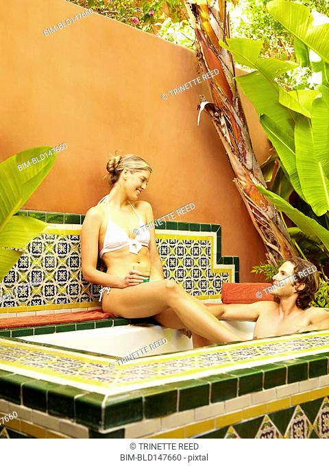 Caucasian couple relaxing in spa hot tub