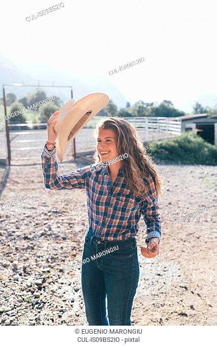Cowgirl putting on stetson in rural equestrian arena