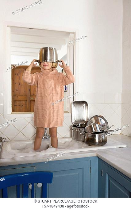 Four year old girl playing in the kitchen sink