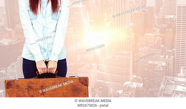 Woman holding suitcase against blue background