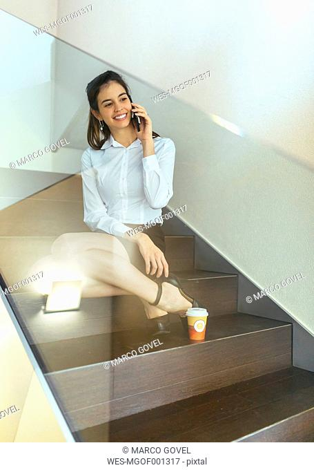 Smiling young businesswoman sitting on steps telephoning with smartphone