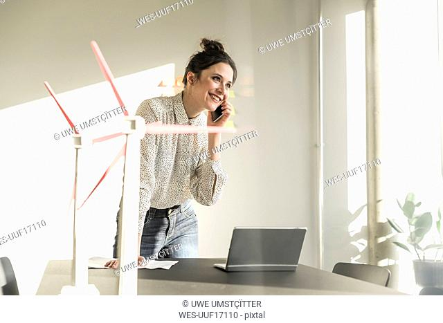 Businesswoman with wind turbine models and laptop on desk in office talking on cell phone