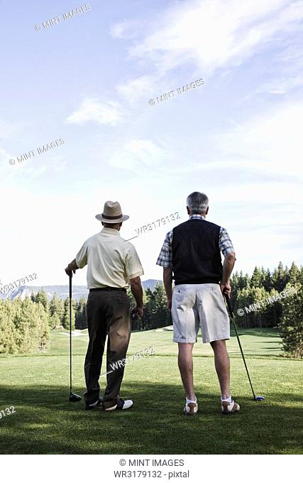 Viewed from behind, a pair of senior golfers check out a fairway on the golf course