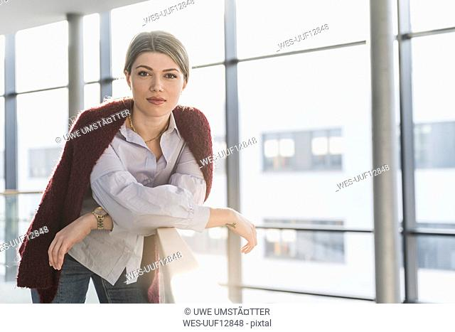 Portrait of confident young woman leaning on railing in bright office building