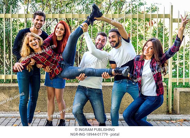 Group portrait of boys and girls with colorful fashionable clothes holding friend. Urban style people having fun - Concepts about youth and togetherness