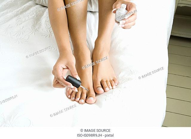 Woman painting toenails