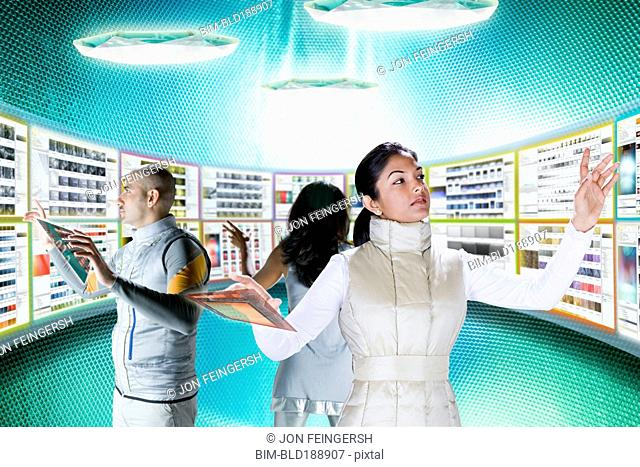 Businesspeople working at futuristic control panels