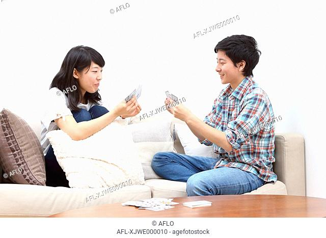 Young Japanese couple playing cards on the sofa