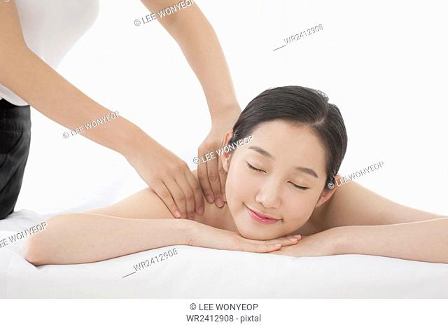 Portrait of young smiling woman getting massage closing her eyes