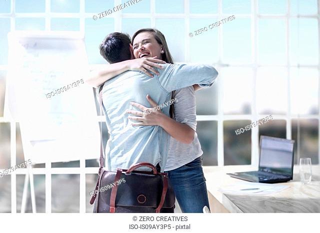 Design colleagues hugging at design studio