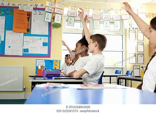 Primary school children raising hands in class, low angle