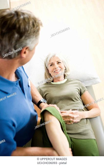 Physical therapist stretching womanÆs leg