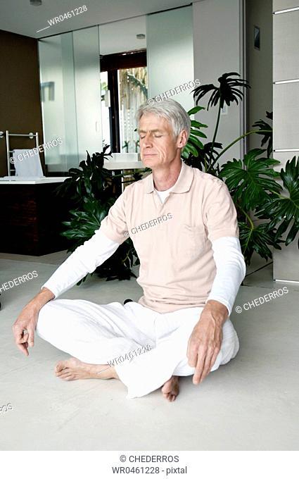 Senior man meditating in a lotus position