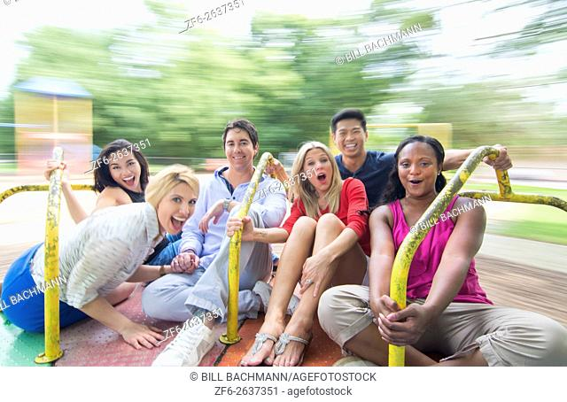 mixed ethnic friends spinning on merry go round in playground laughing with black, vietnamese, hispanic, white people in their 20's and 30's MR-9, MR-5, MR-4
