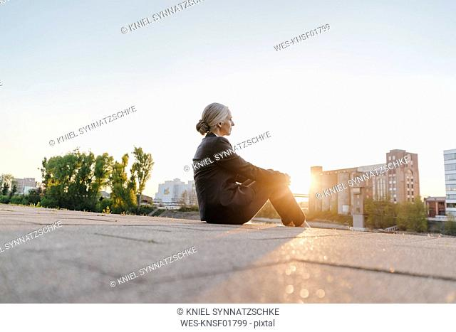 Businesswoman sitting outdoors at sunset