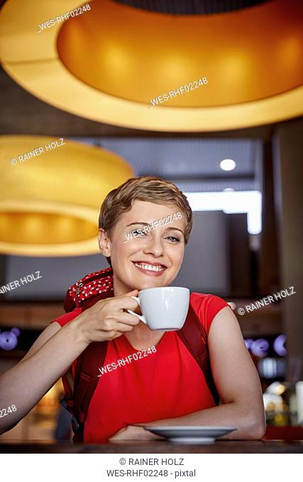 Portrait of smiling woman with backpack in a cafe
