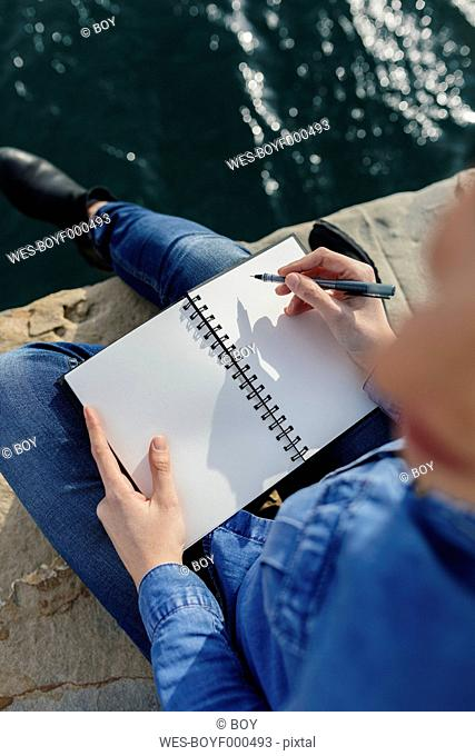 Young woman sitting on dock writing in notebook