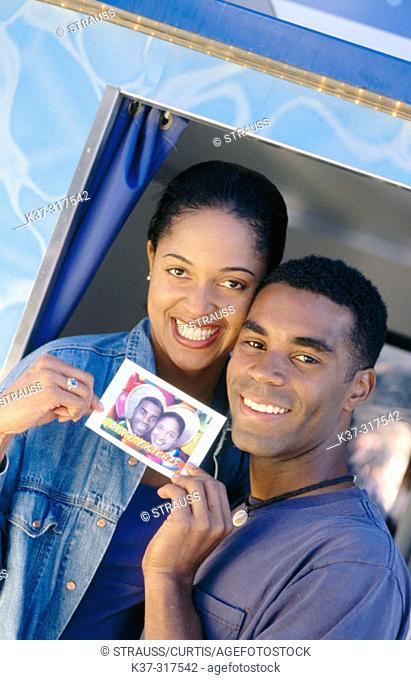 African american couple at photo booth in fun fair