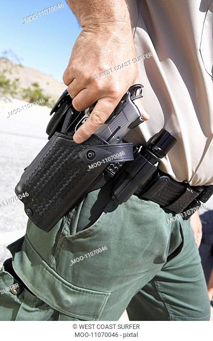 Police officer drawing gun from holster mid section mid section
