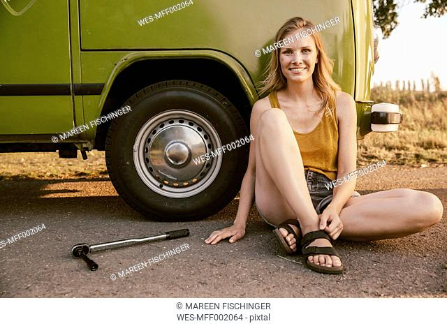 Smiling woman sitting next to a torque wrench at van
