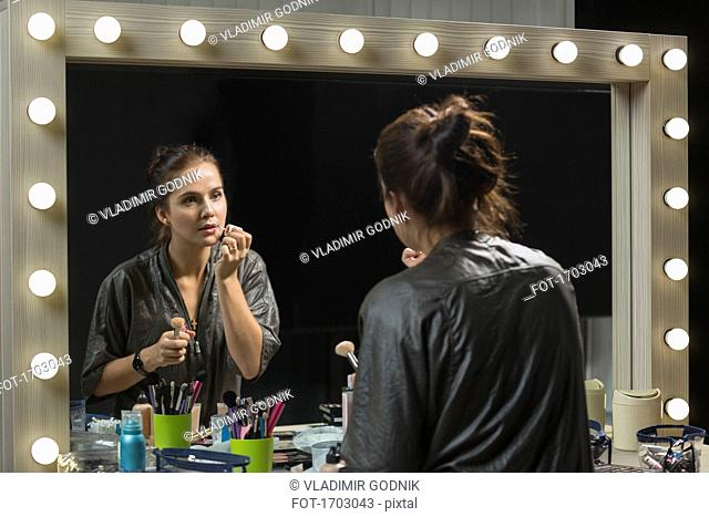 Beautiful woman applying lip gloss in front of mirror