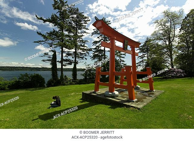 A young girl reads beneath an Asian structure in Seqouia Park overlooking Discovery Passage. Campbell River, Vancouver Island, British Columbia, Canada