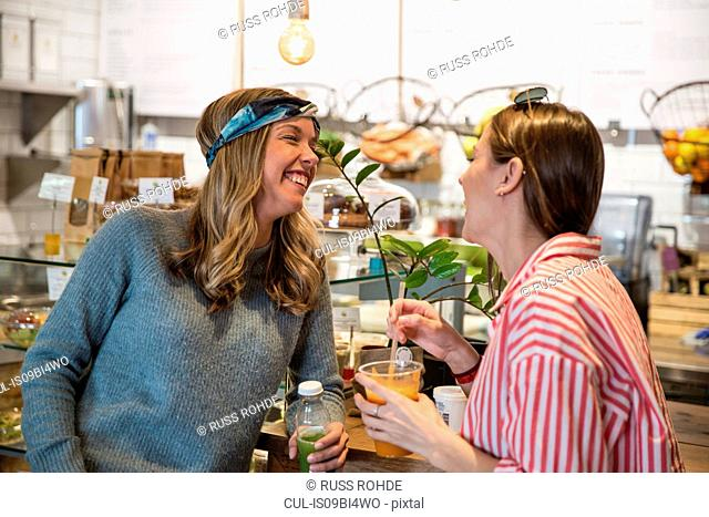 Two young female friends laughing together in cafe