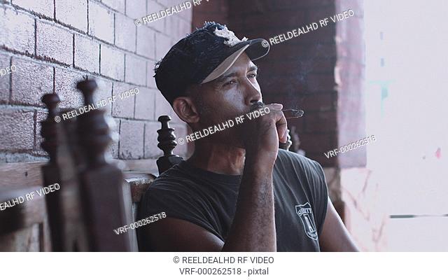 Mature man smoking cigar and looking away